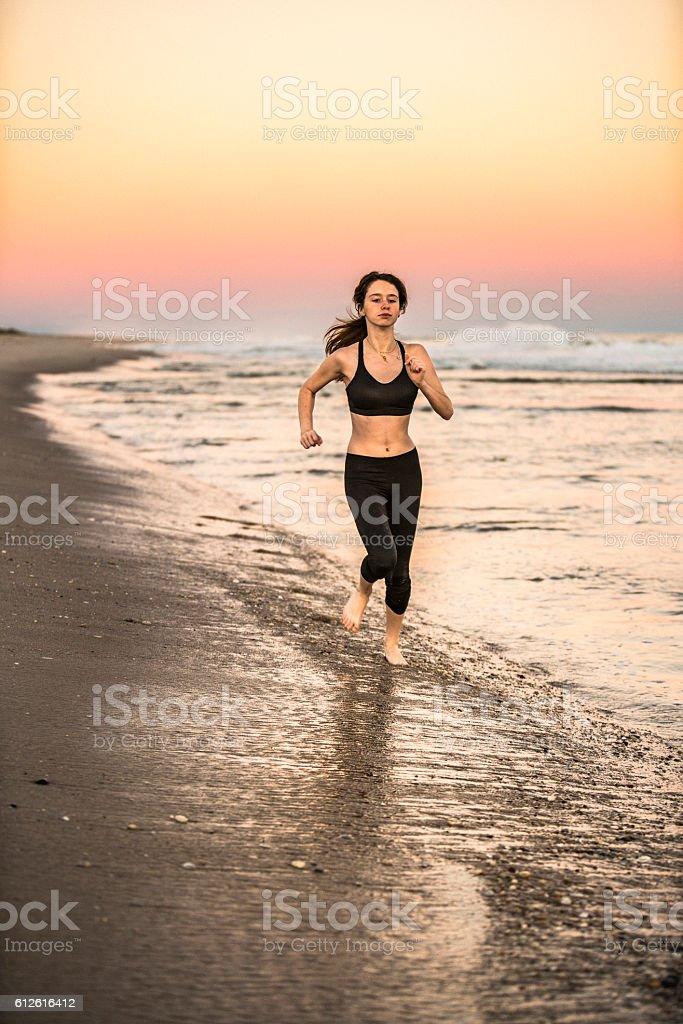Teenager girl running on Hampton Beach, Long Island, USA stock photo