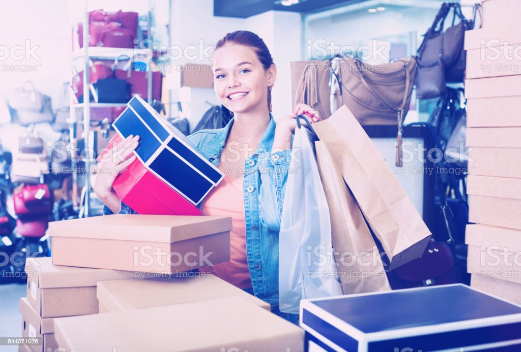 Teenager girl shopping in store with bags stock photo