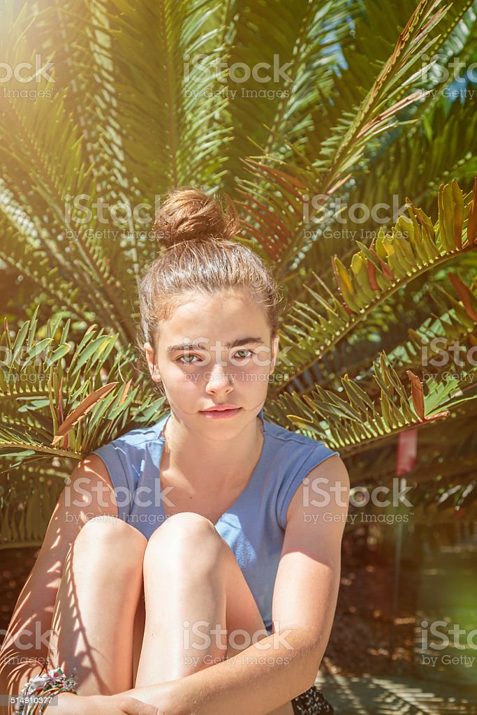 teenager girl, sitting in front of a palm tree stock photo