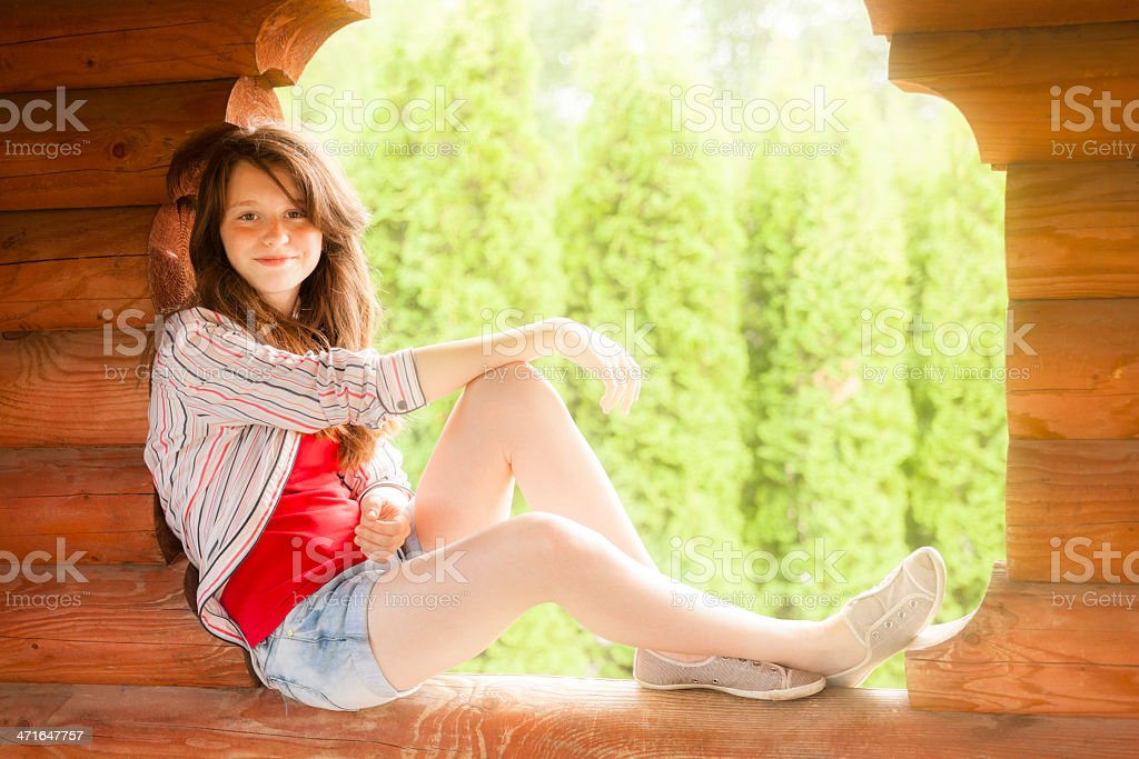 Teenager girl sitting on the window of wooden summer pavilion royalty-free stock photo