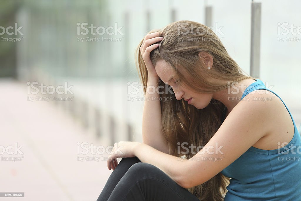 Teenager girl sitting outdoor depressed royalty-free stock photo