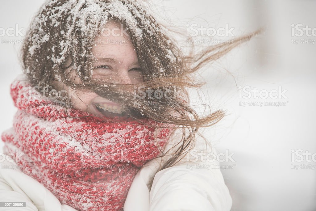 Teenager girl under snowfall at the street stock photo