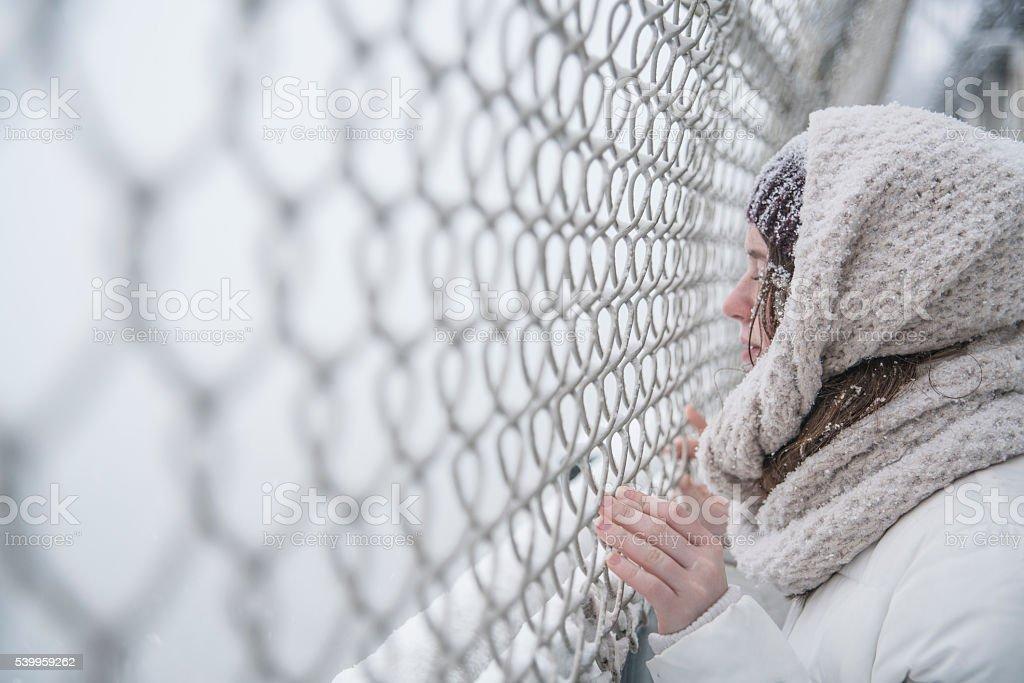 Teenager girl under snowfall at the street stock photo