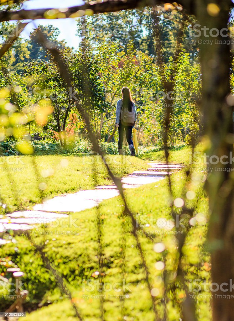 Teenager girl walking on pathway in the park at fall stock photo