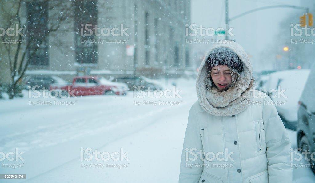 Teenager girl walks under snowfall at the street in Manhattan stock photo