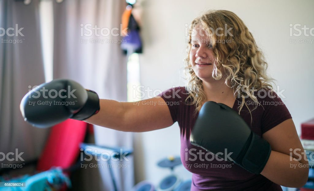 Teenager girl wearing boxing gloves practicing fighting stock photo