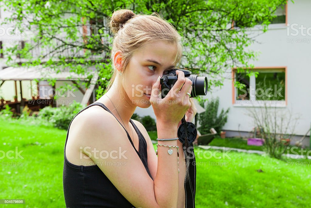 Teenager girl while photographing in the garden stock photo