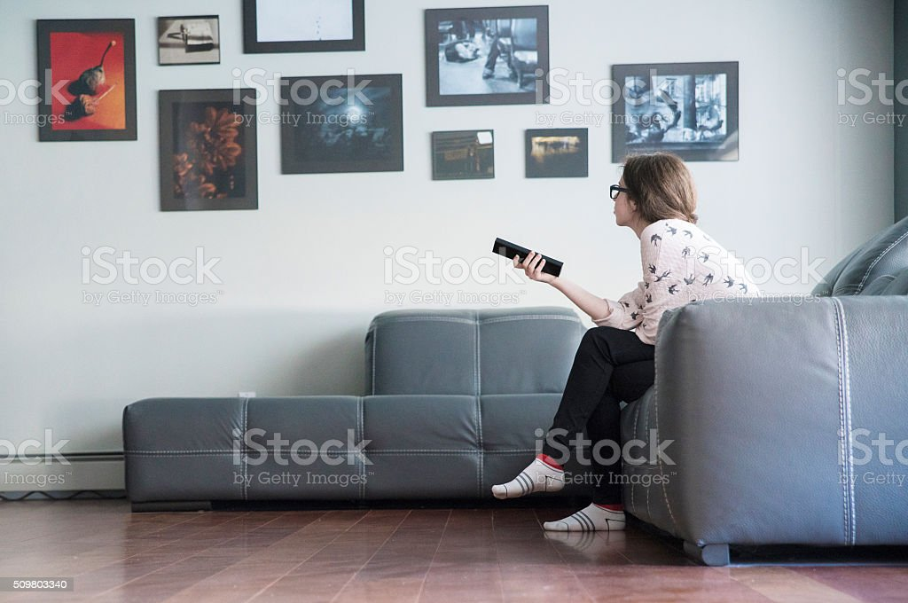 Teenager girl with a TV remote control stock photo