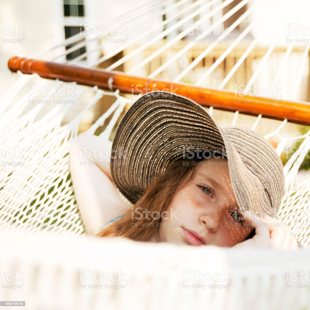 Teenager girl with big hat resting in hammock royalty-free stock photo