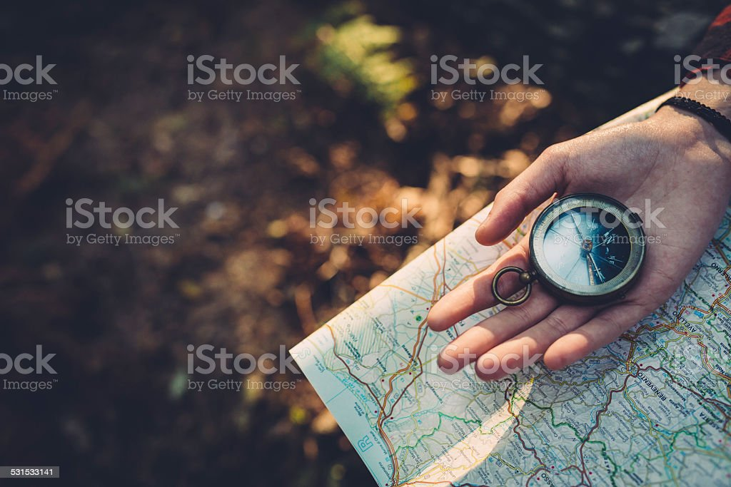 Teenager girl with Compass Reading a Map in the forest stock photo