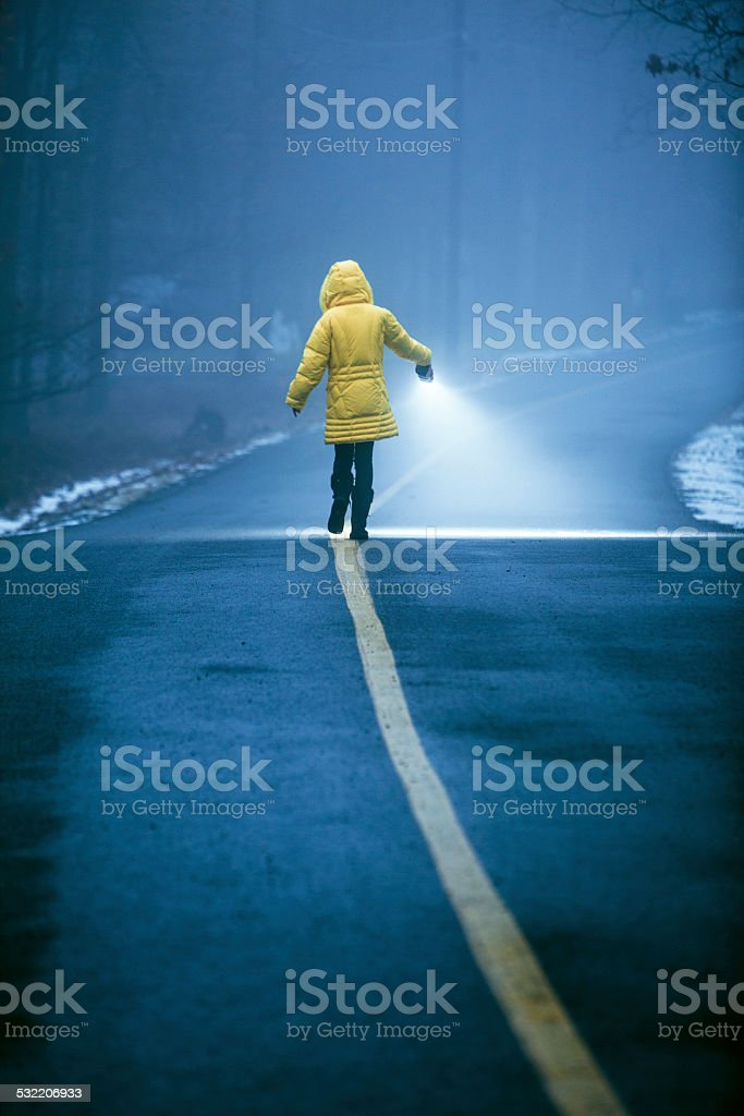 Teenager girl with flashlights walking in the haze stock photo