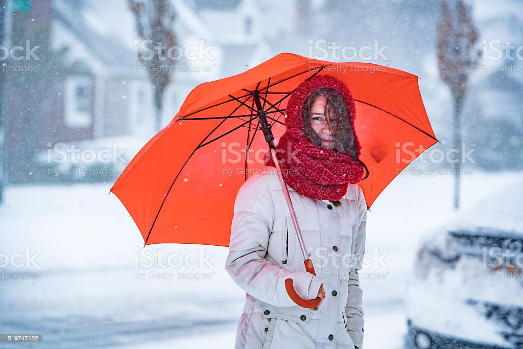 Teenager girl with umbrella under snowfall at the street stock photo