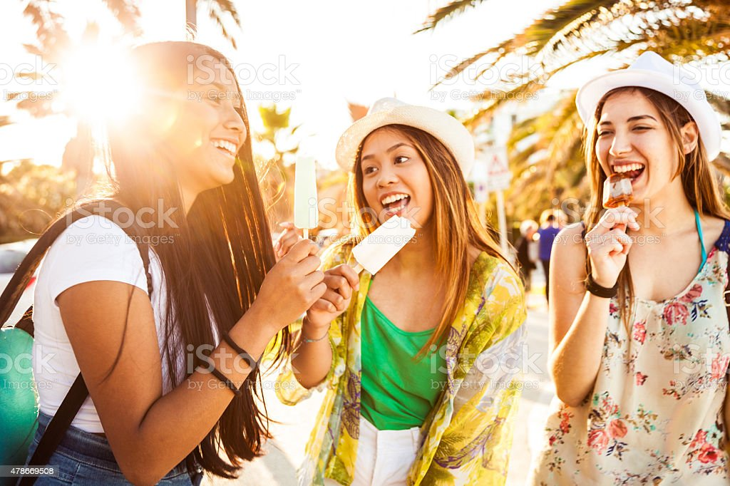 Teenager girls eating an ice cream in summer stock photo