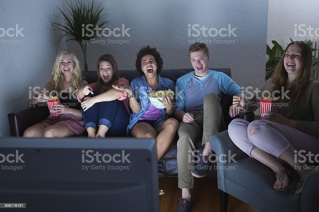 Teenager Group of Friends Watching Humorous Movie, TV Show Together stock photo