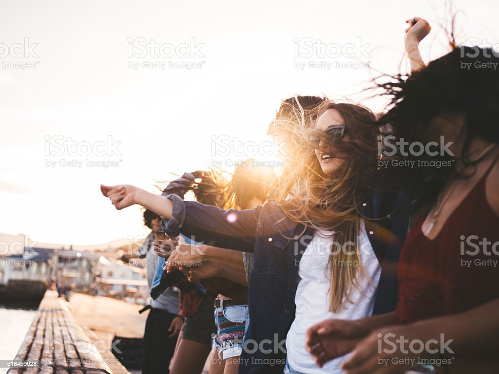 Teenager hipster style friends dancing on the pier at sunset stock photo
