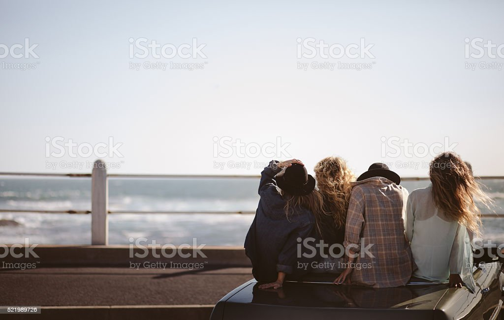Teenager hipster styled friends watching the sea from their conv stock photo