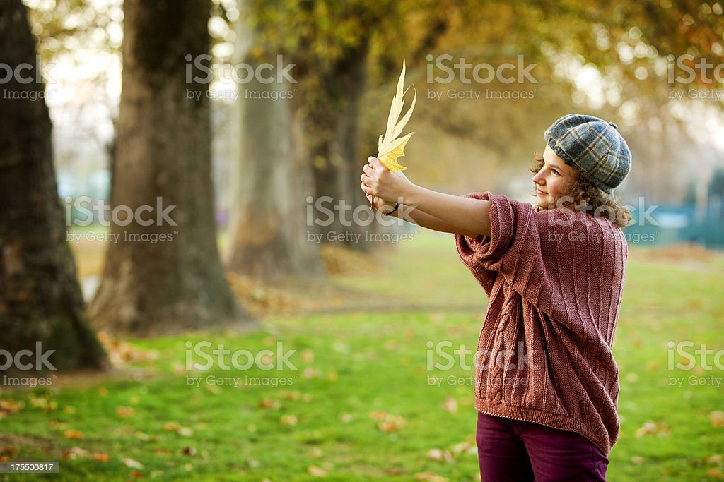 teenager holding autumn maple leaf royalty-free stock photo