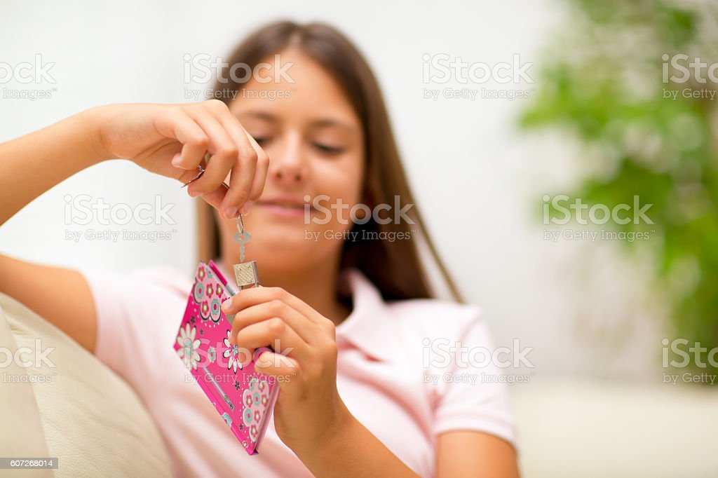 Teenager holds the key of the diary, keeps her secrets stock photo