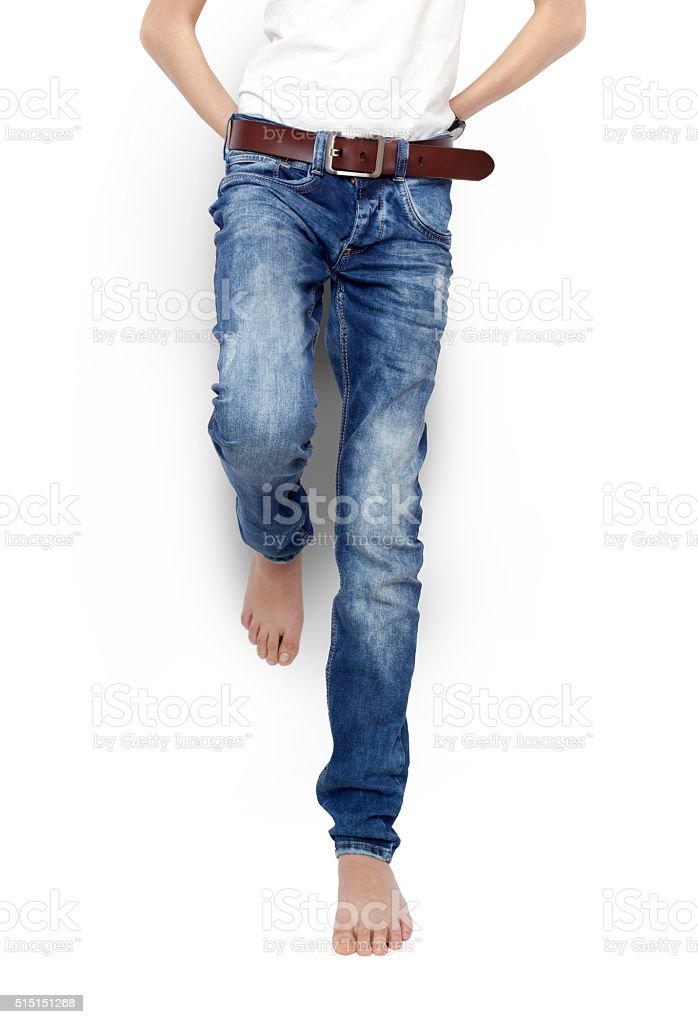 Teenager in blue jeans and a white t-shirt, barefoot, isolated. stock photo