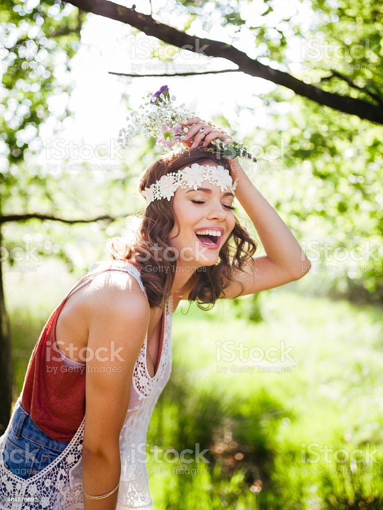 Teenager in boho style laughing happily in a summer park stock photo