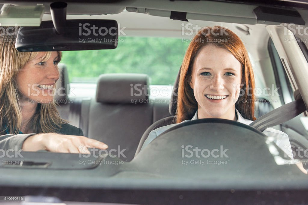 Teenager in car with driving instructor stock photo