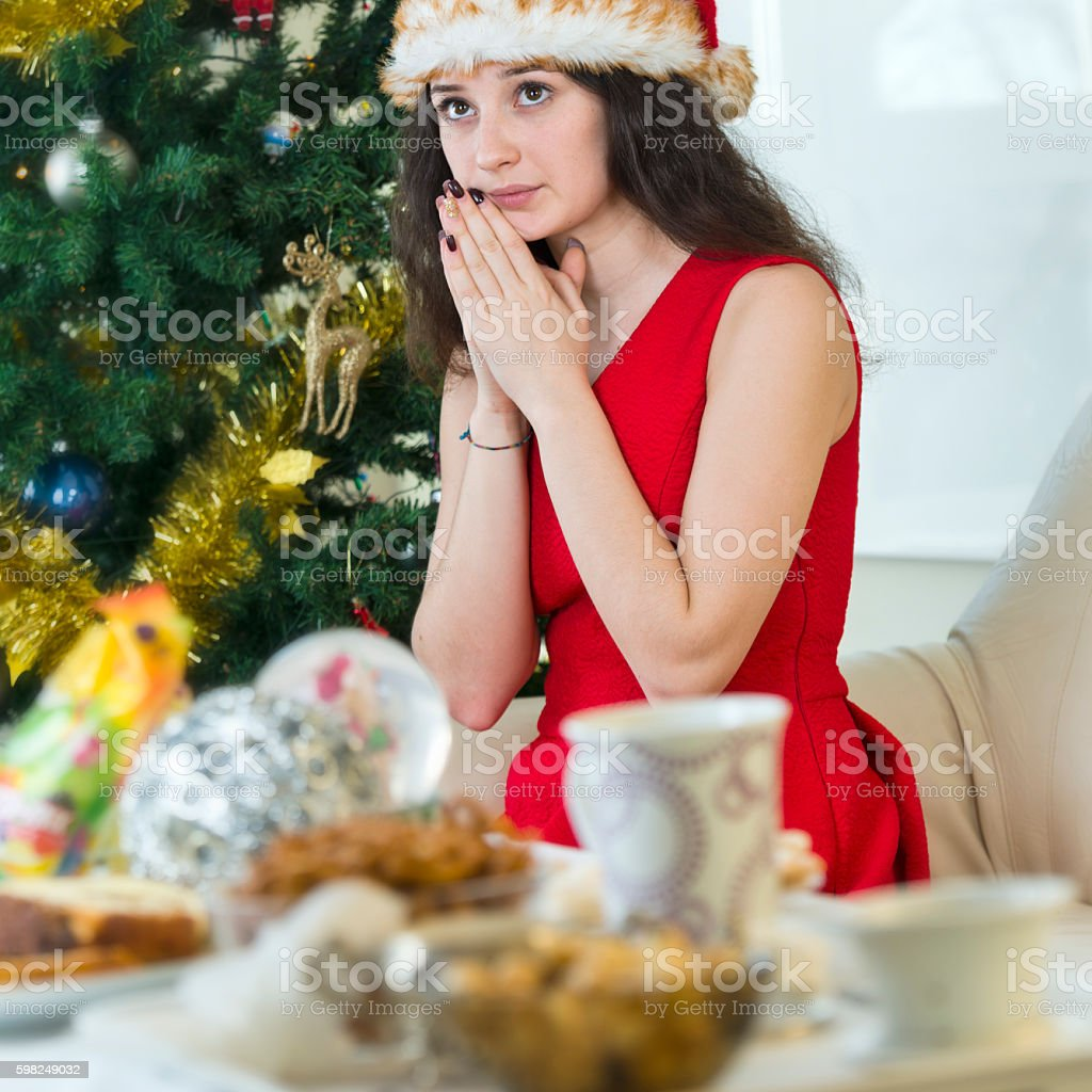 Teenager in Christmas outfit praying stock photo