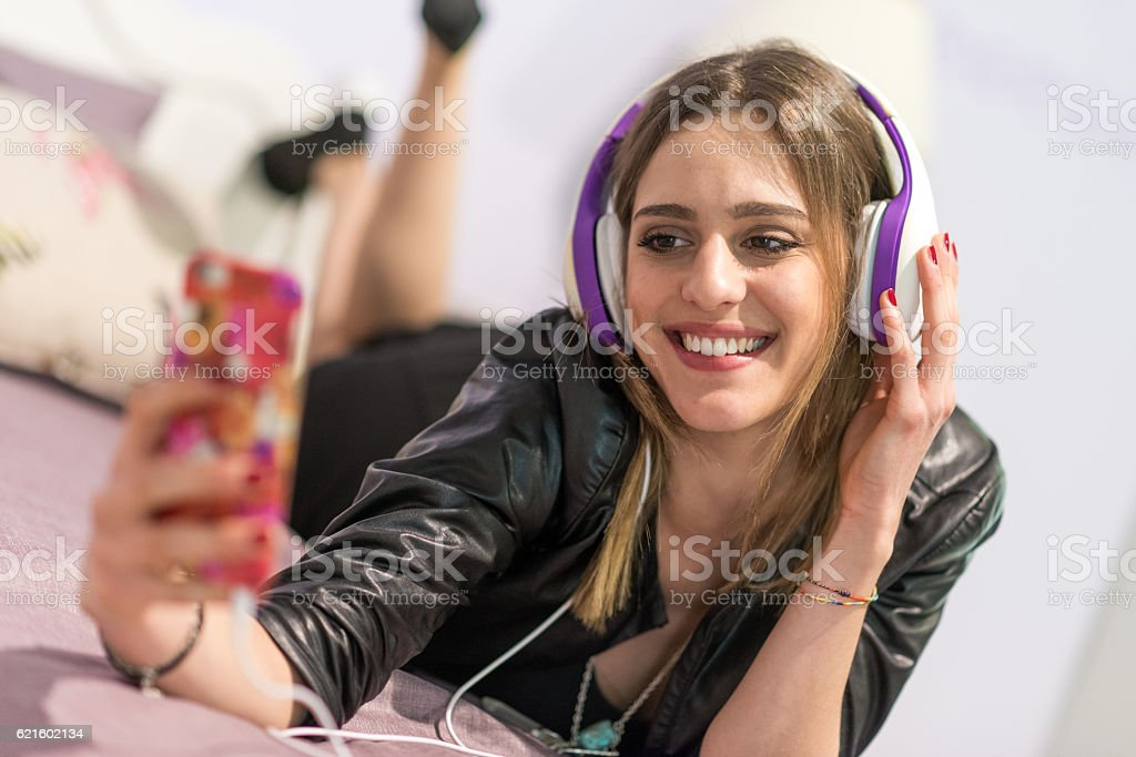 Teenager in her bedroom listening to music with smartphone stock photo