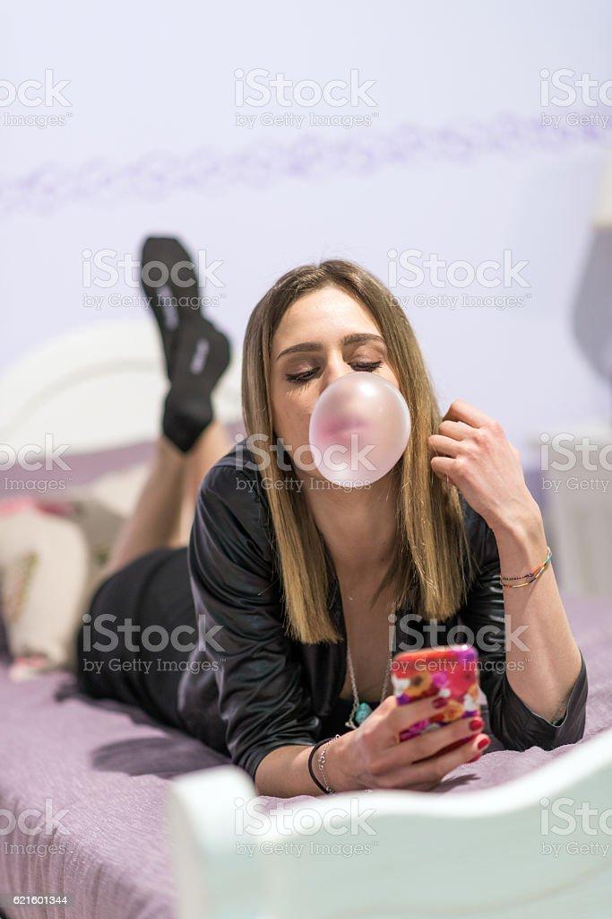 Teenager in her bedroom using smartphone stock photo