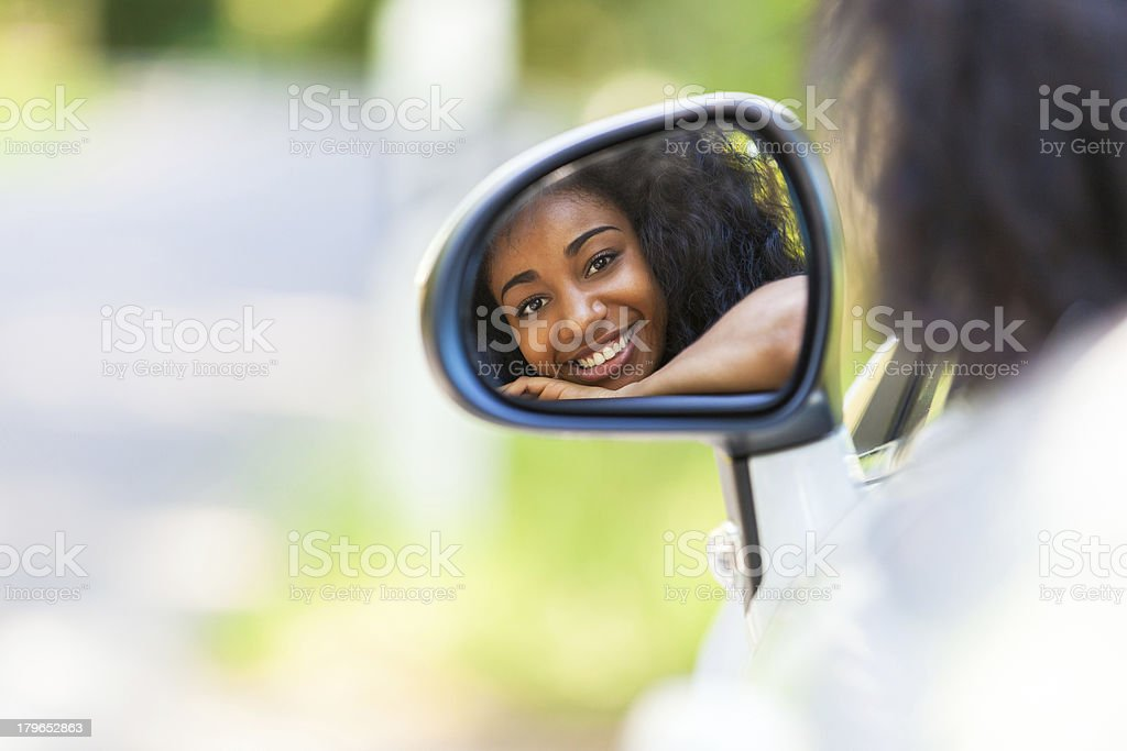 A teenager in the rear view mirror of her new convertible stock photo