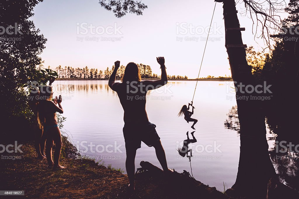 Teenager jumping into the lake stock photo