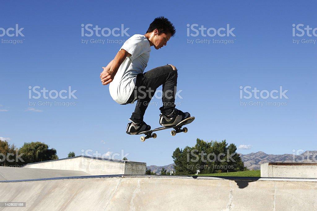 Teenager jumping on skateboard royalty-free stock photo