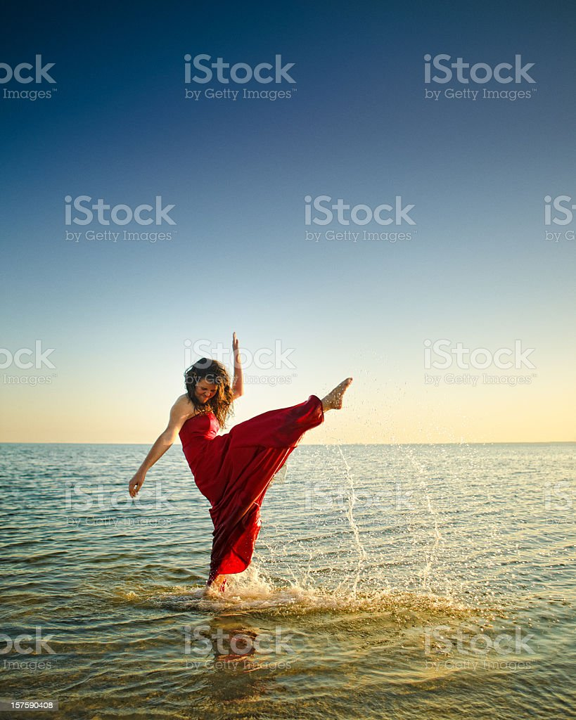teenager kicking high with her foot in the beach stock photo