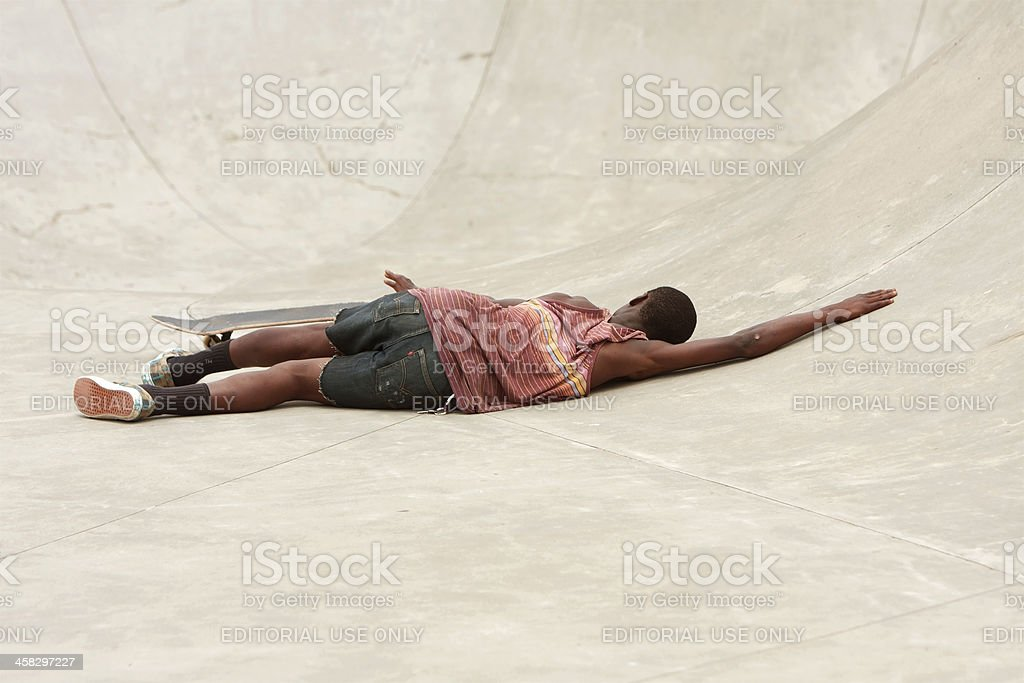 Teenager Lays On Concrete After Wiping Out During Skateboard Run royalty-free stock photo