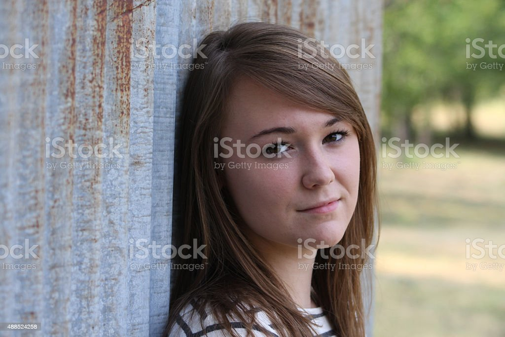 Teenager leaning against a metal wall stock photo