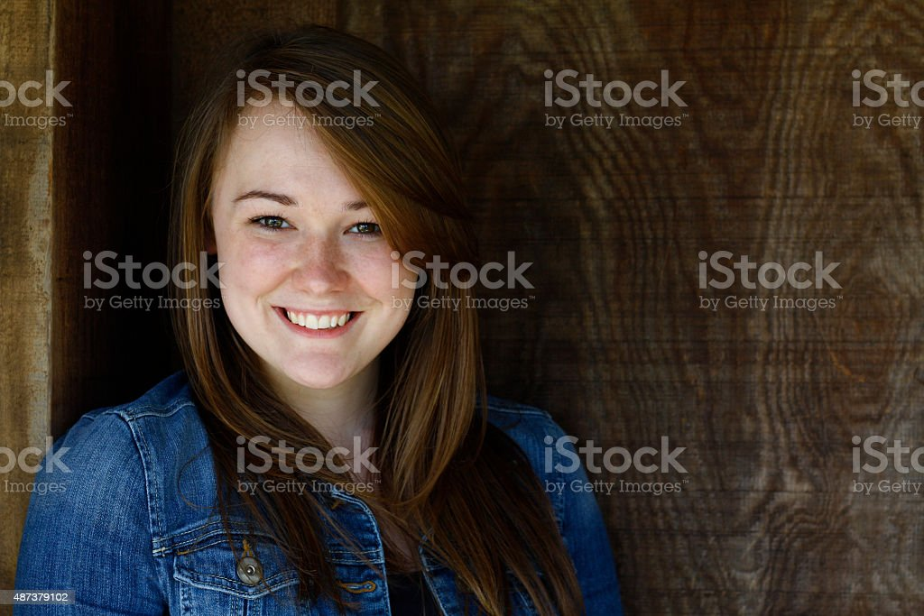 teenager leaning against a wood door stock photo