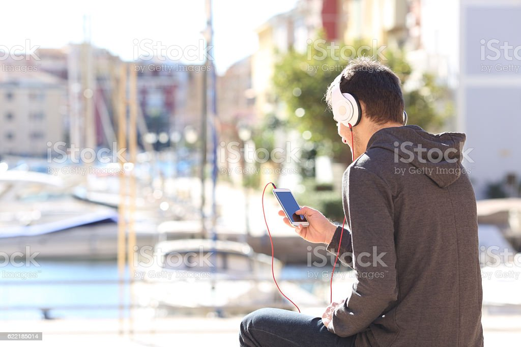 Teenager listening music from smart phone stock photo