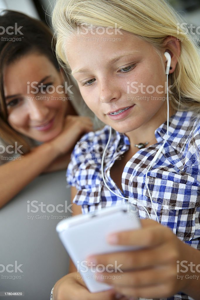 Teenager listening to music on smartphone with adult beside her royalty-free stock photo