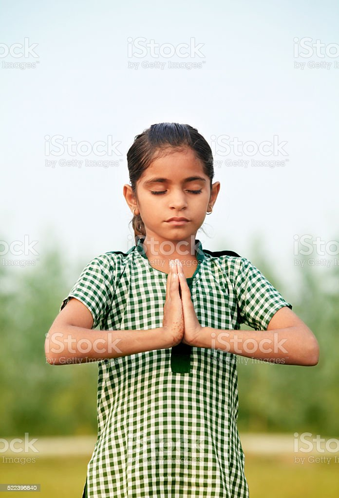 Teenager little girl praying in the nature stock photo