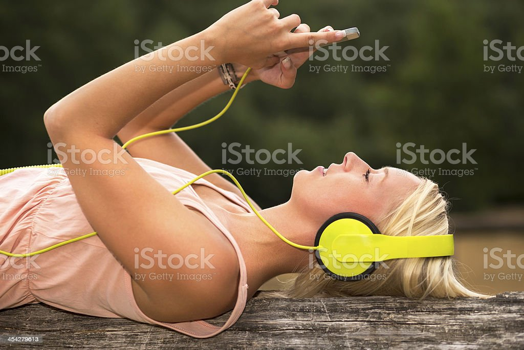 Teenager lying with headphone and smartphone outdoors stock photo