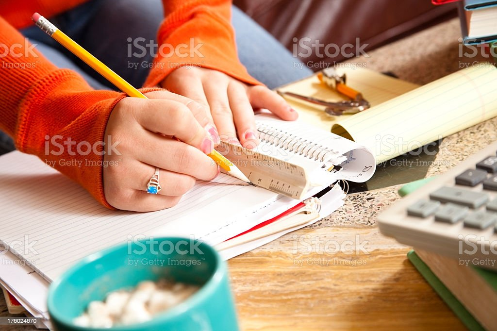 Teenager on sofa doing her homework at coffee table royalty-free stock photo