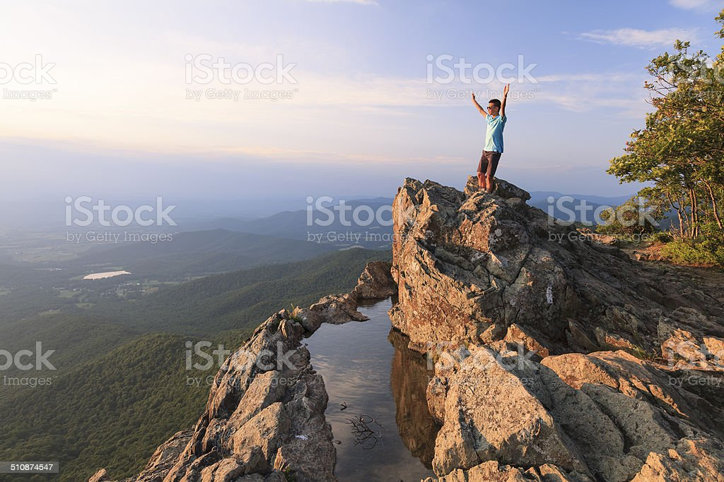 Teenager on the edge of a cliff stock photo