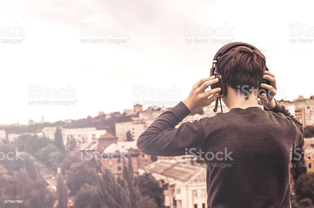 teenager on the roof of the house in the headphones stock photo