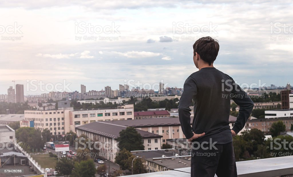 teenager on the roof of the house stock photo