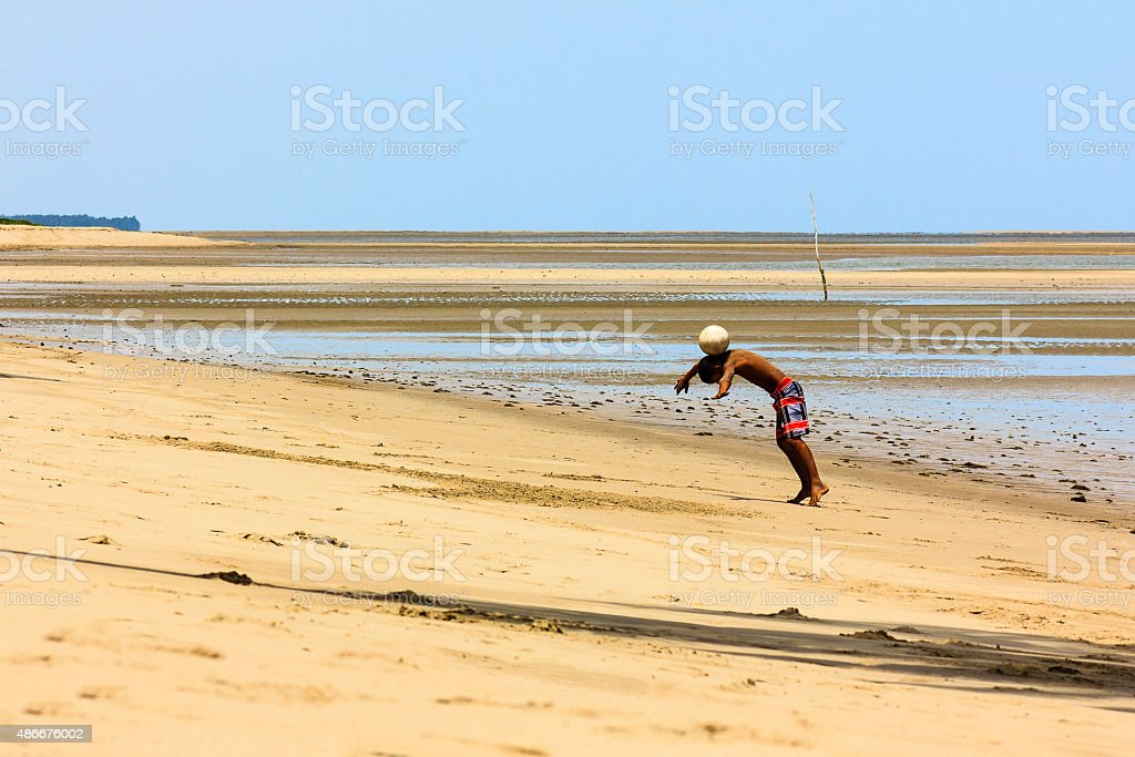 Teenager Playing Football at Beach in Low Tide stock photo
