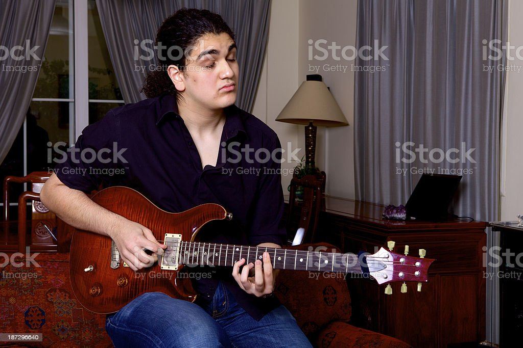 Teenager playing the electric guitar stock photo