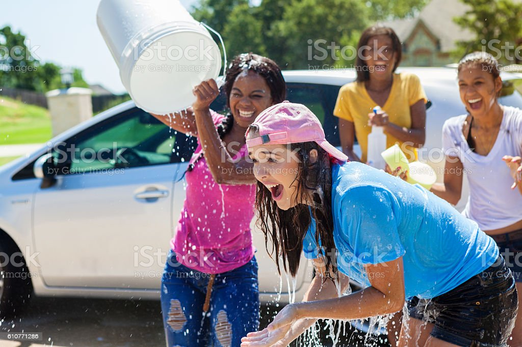 Teenager pours bucket of water on friend at car wash stock photo