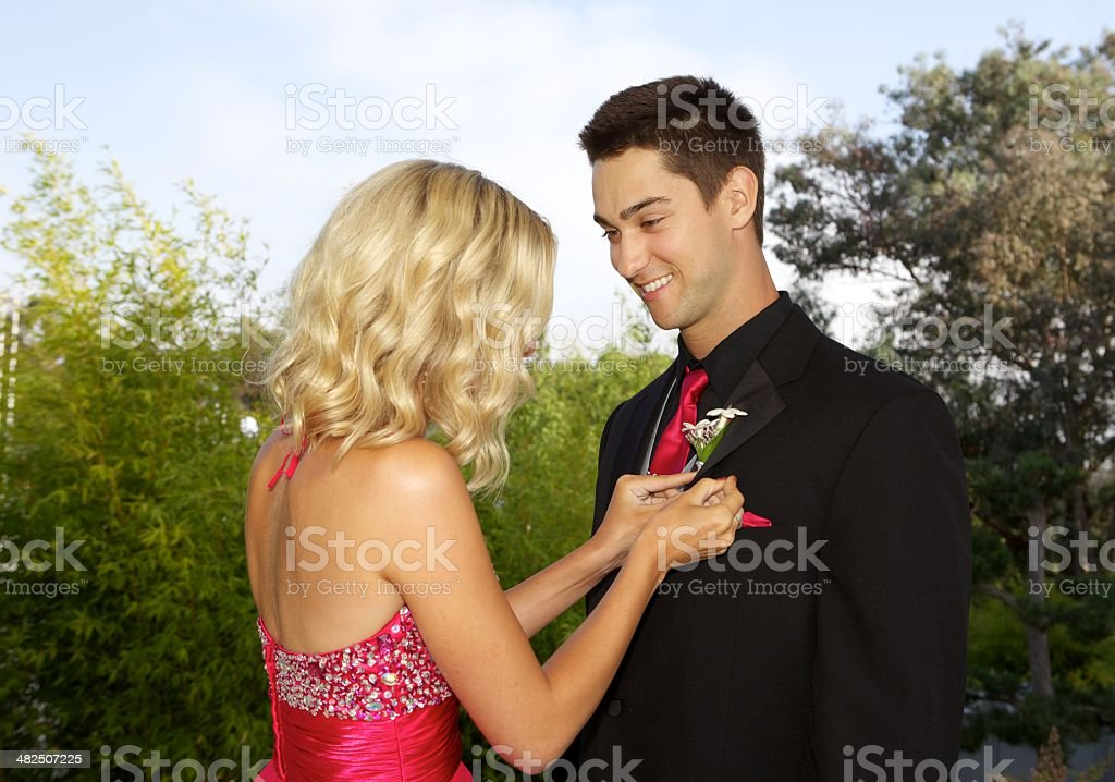 Teenager Prom Couple - Girl Putting Boutonniere  On Her Date royalty-free stock photo