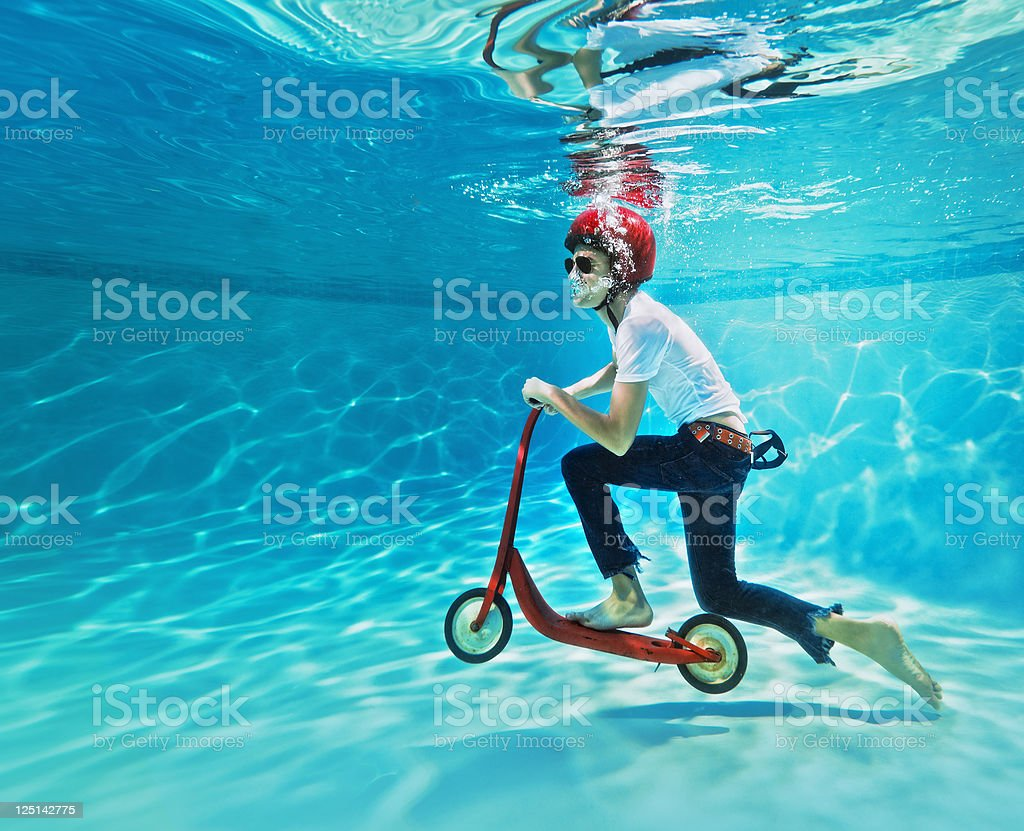 teenager pushing a scooter underwater stock photo