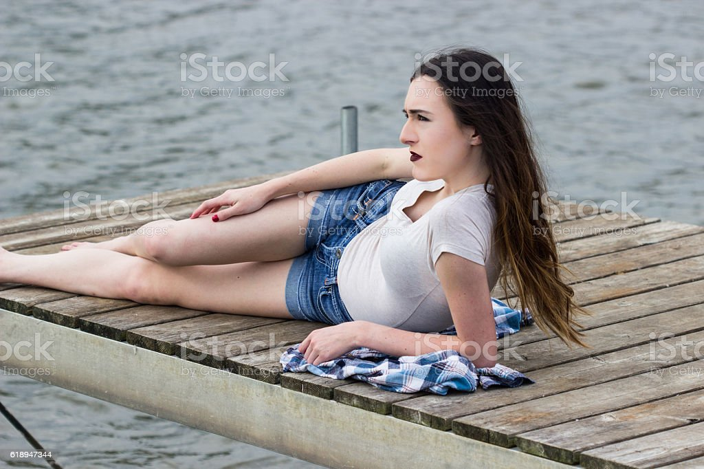 Teenager Relaxes on Pier stock photo