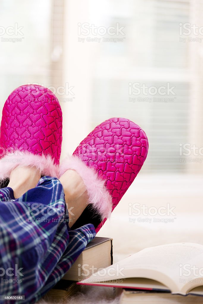 Teenager relaxing, reading books in her pajamas and fun slippers. stock photo